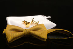 Deluxe. Gold bow tie, white silk pocket handkerchief and gold cufflinks on a glass surface royalty free stock photos