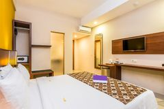 Deluxe Hotel Bedroom. Image of deluxe bedroom at cheap prices hotel in Bali. The wall painted with bright color. The bed looks very soft and comfortable royalty free stock photo