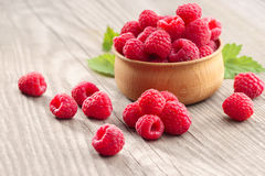 Deluxe Raspberries in bowl on wooden table. Close up, high resolution product. Harvest Concept Royalty Free Stock Photo