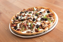 Deluxe Thin Crust Pizza. Pizza texture with olives on wood table Stock Images