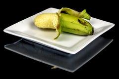 Delvist mogen och klart ringd banan att äta Arkivbilder