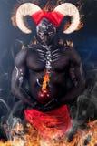 Demónio impetuoso Um demônio ardente com chifres e uma maçã de desacordo imagem de stock royalty free