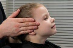 Dem Mädchen wird eine Kopfmassage gegeben, bevor man das Haar anredet stockfotografie