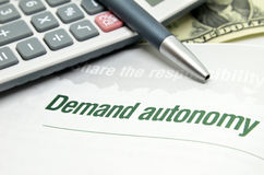 Demand autonomy printed on book. With calculator and pen Royalty Free Stock Image