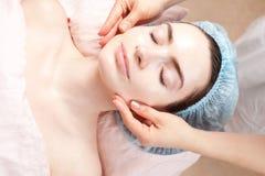 Demande de règlement de beauté de jeune femme - massage facial Photographie stock libre de droits