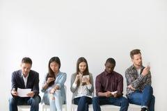 Demandeurs multi-ethniques se préparant à l'entrevue d'emploi attendant dans le qu images stock