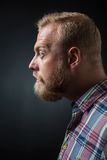 Demanding bearded man. Profile of demanding bearded man on black background. Short-haired blond man googling his eyes Royalty Free Stock Image