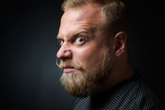 Demanding bearded man. Profile of demanding blond bearded man on black background. Serious man looking so strange and narrowing his eyes because of annoyance Stock Images