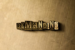 DEMANDING - close-up of grungy vintage typeset word on metal backdrop Royalty Free Stock Image