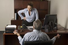 Demanding explanations. Attractive young executive woman demanding explanations from an elder employee in her office Royalty Free Stock Photos