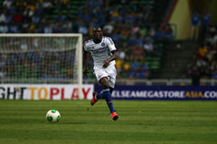 Demba Ba. SHAH ALAM - JULY 21: Chelsea Football Club player Demba Ba (white jersey) controls the ball in a friendly match with the Malaysian national team in Royalty Free Stock Photo