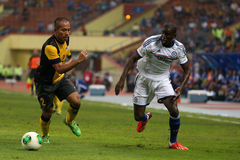Demba Ba. SHAH ALAM - JULY 21: Chelsea Football Club player Demba Ba (white jersey) dribbles past Mahalli Jasuli (yellow/black) in a friendly match with the Royalty Free Stock Images