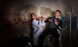 Demented scientist and patient in dungeon Stock Photography