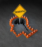 Dementia Handicap. Concept as a group of three dimensional traffic cones shaped as a human head with a warning road sign emerging out of  a hole in the street Stock Photo