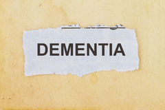 Dementia. Newspaper cutout in an old paper background Royalty Free Stock Photo