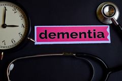 Dementia on the print paper with Healthcare Concept Inspiration. alarm clock, Black stethoscope. royalty free stock photo