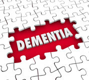 Dementia Puzzle Pieces Hole Aging Memory Loss Alzheimer's Diseas. Dementia word in a hole with puzzle pieces to illustrate aging, memory loss, mind or brain Royalty Free Stock Photo