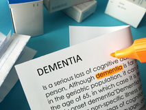 Dementia treatments. The word dementia highlighted in orange with felt tip pen. Drugs in the background royalty free stock photo