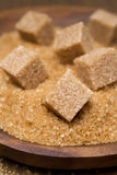 Demerara sugar and brown sugar cubes in a bowl, selective focus Stock Image