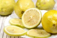 Demi citron et tranches près de plusieurs pleins citrons Photographie stock