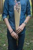 Demi corps de l'homme en fleur de prise de main de chemise de blue-jean Photographie stock