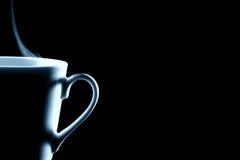 Demi de tasse de café de cuisson à la vapeur sur le noir Images libres de droits