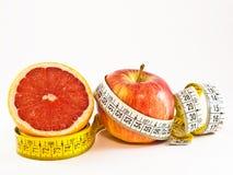 Demi de pamplemousse et de pomme avec la mesure de bande photographie stock