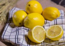 Demi et entiers citrons mûrs sur le tissu Image stock