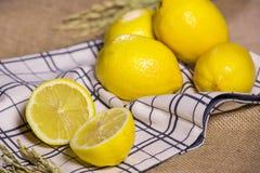 Demi et entiers citrons mûrs sur le tissu Images stock
