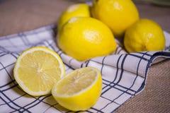 Demi et entiers citrons mûrs sur le tissu Photographie stock libre de droits