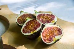 Demi figues rouges sur sain exotique mûr frais de fond en bois Photographie stock