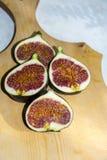Demi figues rouges sur sain exotique mûr frais de fond en bois Photographie stock libre de droits