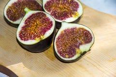Demi figues rouges sur sain exotique mûr frais de fond en bois Photo stock