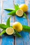 Demi les citrons entiers et coupés frais souhaitent des feuilles sur le vieux fond bleu en bois Photographie stock