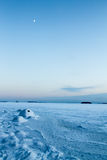 Demi-lune au-dessus de glace de mer pendant l'heure de bleu d'hiver Image stock