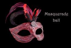 Demi masque de carnaval rouge vénitien avec des plumes, au fond noir Image libre de droits