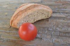 Demi pain de farine noire et de tomatoe rouge Image stock