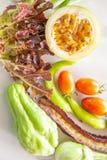Demi passiflore comestible de passiflore, laitue de chêne rouge, tomates, poivrons doux, haricot à ailes pourpre, chayote et aube images libres de droits