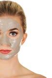 Demi visage de jeune femme avec le masque facial Image stock