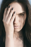 Demi visage de jolie bâche de femme avec la main image stock