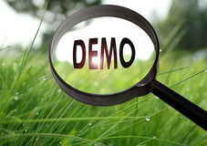 Demo. Magnifying glass with the word demo on grass background. Selective focus Stock Images