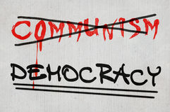 Democracy. No for communism, yes for democracy. Crossed sign Communism versus underlined sign Democracy on the grey wall Stock Illustration