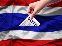 Democracy and elections in Thailand concept. close up hand. Of a person casting a ballot at elections during voting on canvas Thailand flag background royalty free stock images