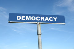 Democracy signpost. Metal signpost spelling Democracy over blue sky stock images