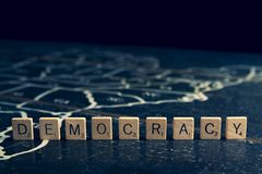 Democracy spelled with Scrabble tiles on map of United States. Democracy spelled with Scrabble tiles on rustic wooden map of United States stock photo