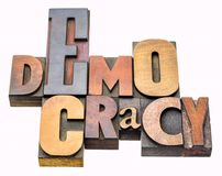 Democracy word abstract in wood type. Democracy - isolated word abstract in vintage letterpress wood type printing blocks stained by color inks stock image
