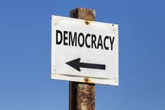 Democracy word and arrow signpost. On clear sky background. Motivational sign royalty free stock photos