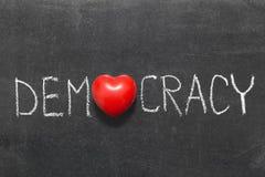 Democracy. Word handwritten on blackboard with heart symbol instead of O stock photo