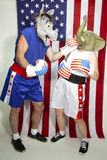 Democrat beating up a Republican. Man in donkey mask (Democrat) punching woman in elephant mask (Republican) in front of an american flag Royalty Free Stock Image