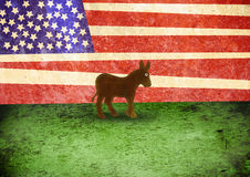 Democratic Donkey. A distressed textured image of the Democratic donkey standing on grass in front of an American flag Stock Images